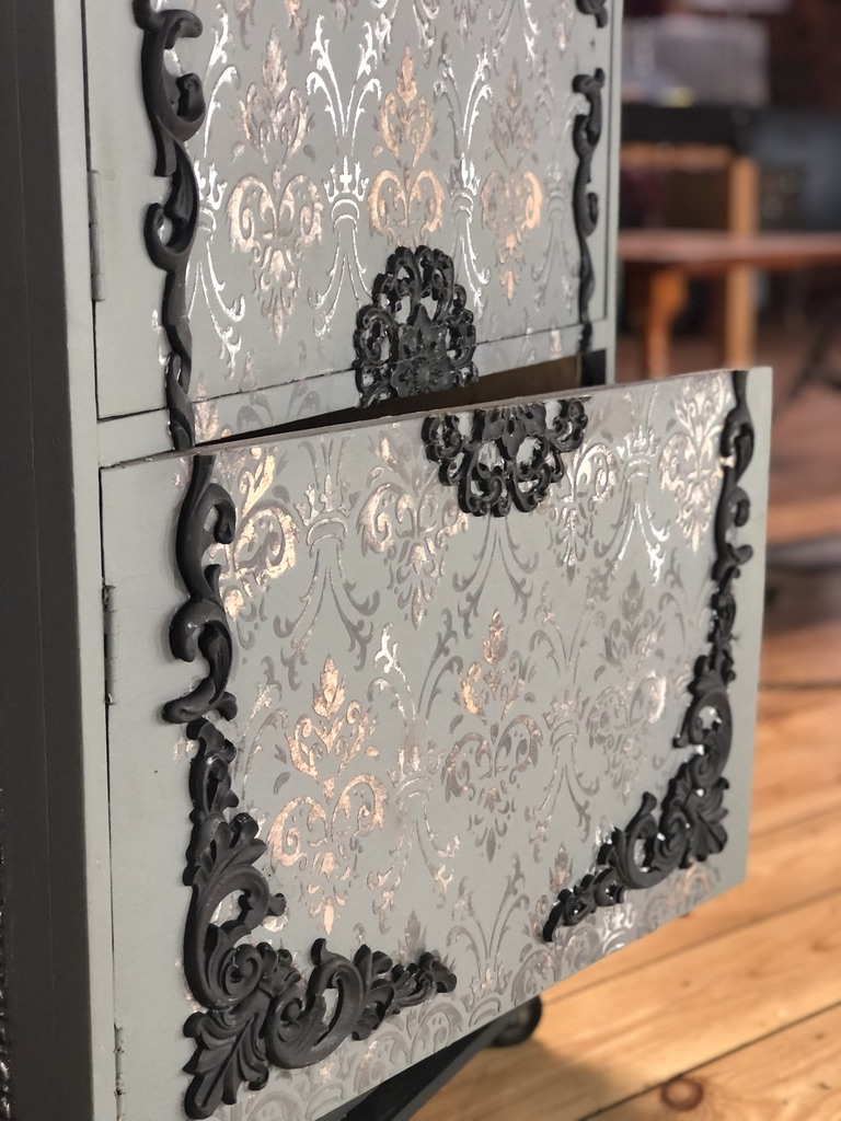 A close up showing the door of the furniture art project ajar where the mouldings had been sliced.