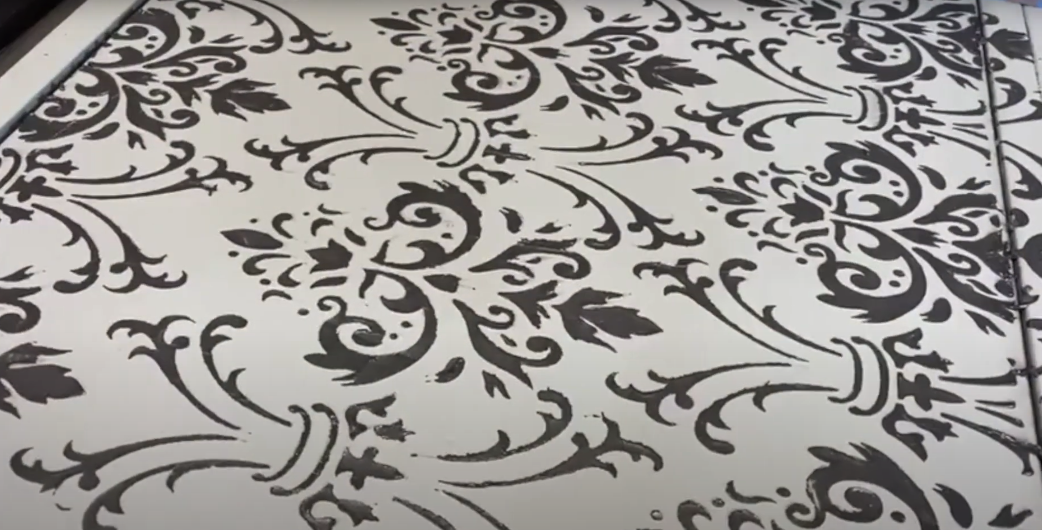 Close up of black raised stencilling against a grey background on the front of a furniture art piece
