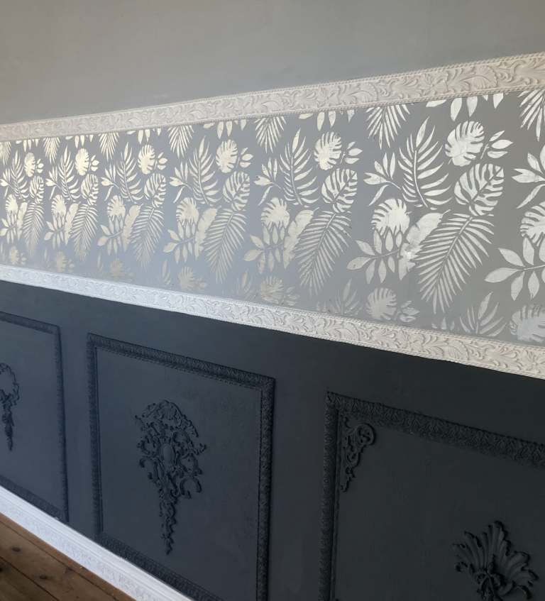 A finished interior design accent wall with silver raised stencilling between two woodubend trims acting as dado rails. Three panels on the bottom have been painted over in a dark grey, giving way to a lighter grey at the top, seperated by white woodubend trim