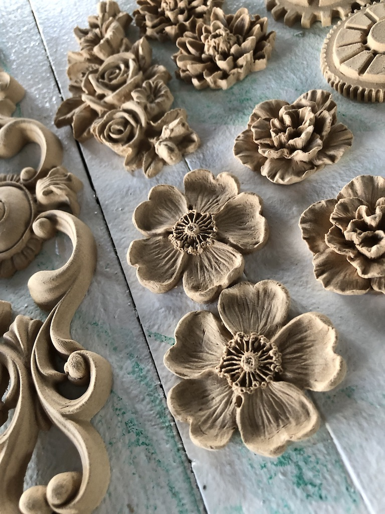 A selection of brown WoodUbend mouldings placed on a rustic white table