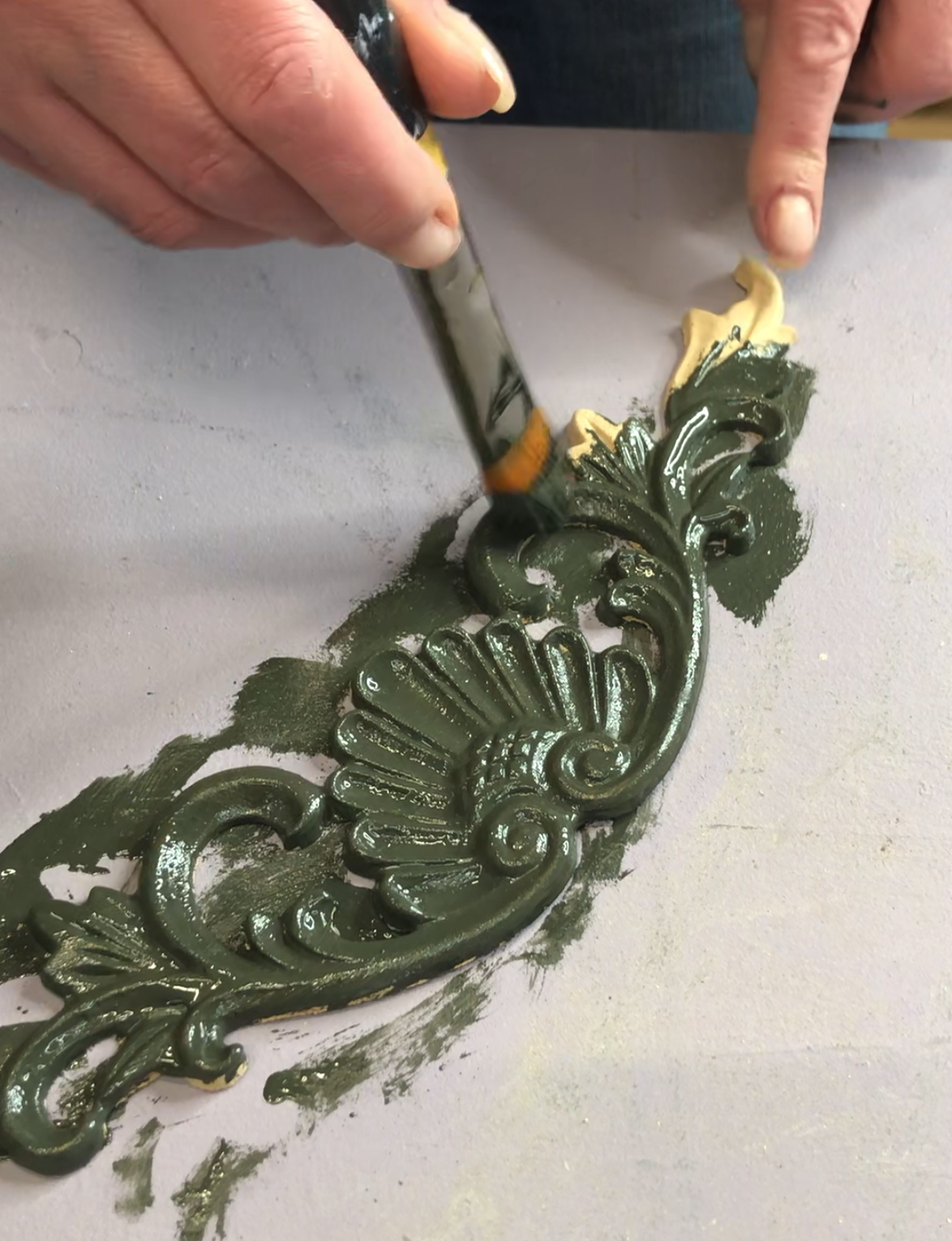 A WoodUbend moulding being pre painted in a grey green colour. The paint is still fresh and you can see the reflection of the light.