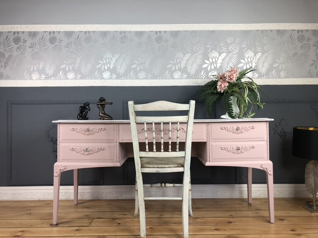 A pink desk with a white chair set in front of a dark and light grey wall with silver stencilling