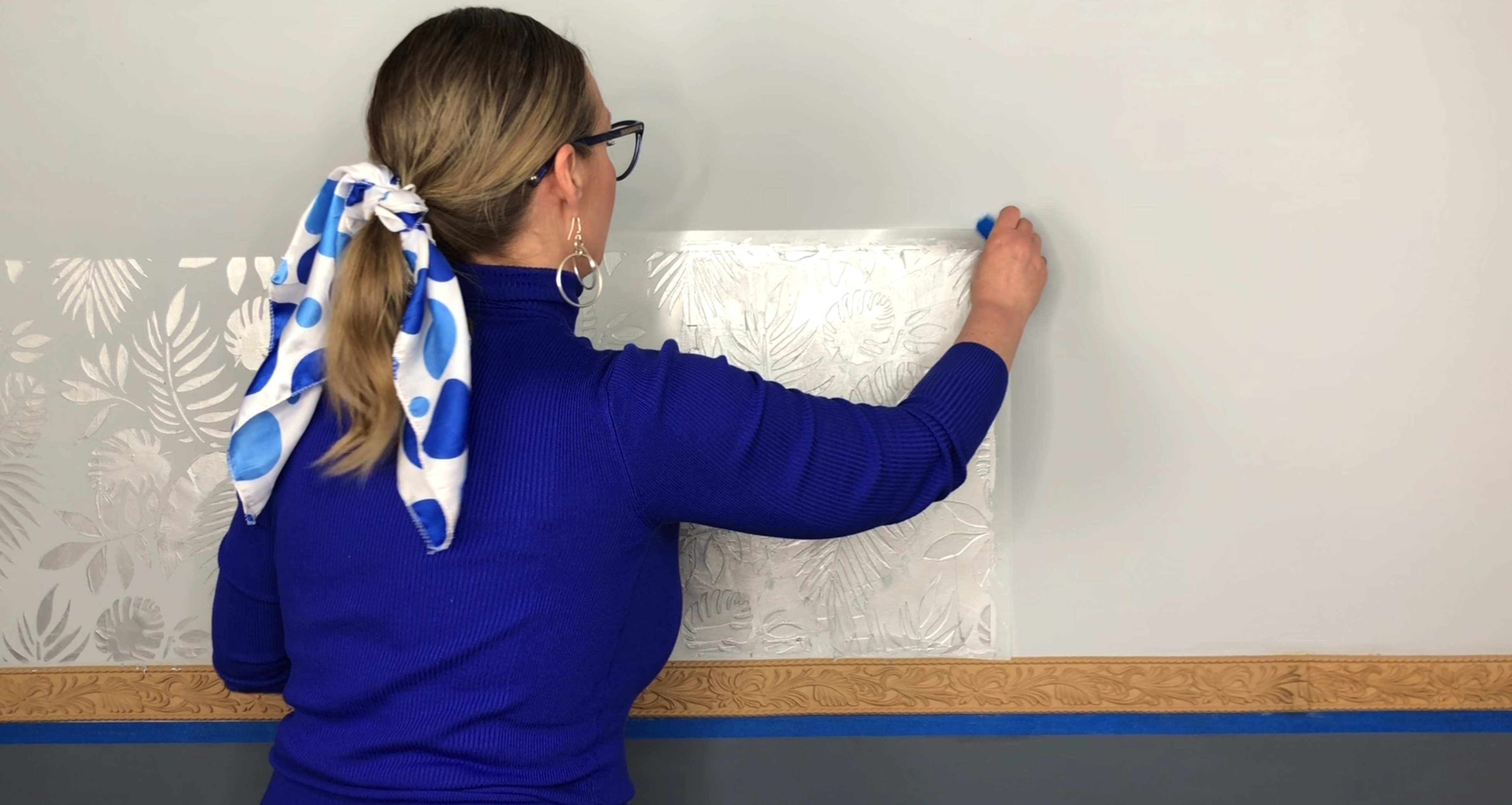 a woman in blue removing a stencil covered in silver paint revealing the leaf pattern underneath