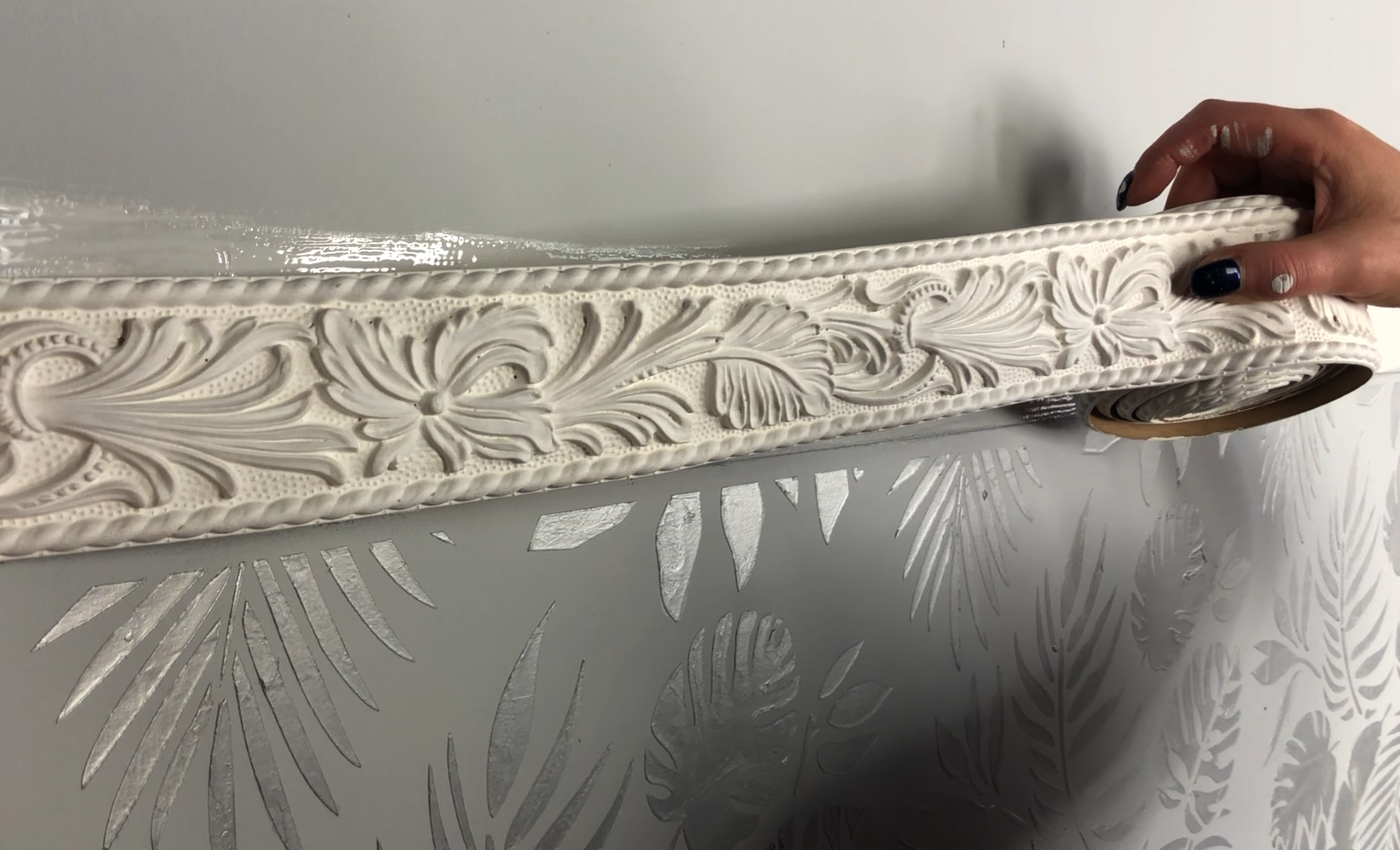 Pre-painted woodubend trim being adhered to a wall. It is painted white and the raised stencilling of the interior design project is visible at the bottom