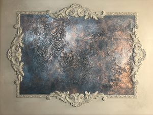Final staged shot of a wall decor project, there is blue and bronze texture framed by white woodubend