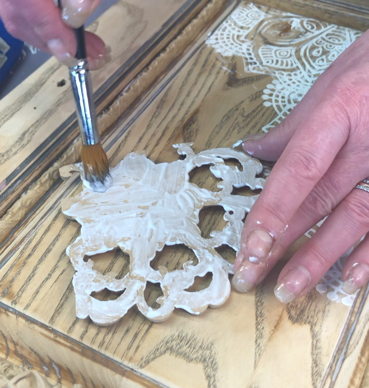 White wood glue being applied with a paintbrush to the back of a WoodUbend moulding