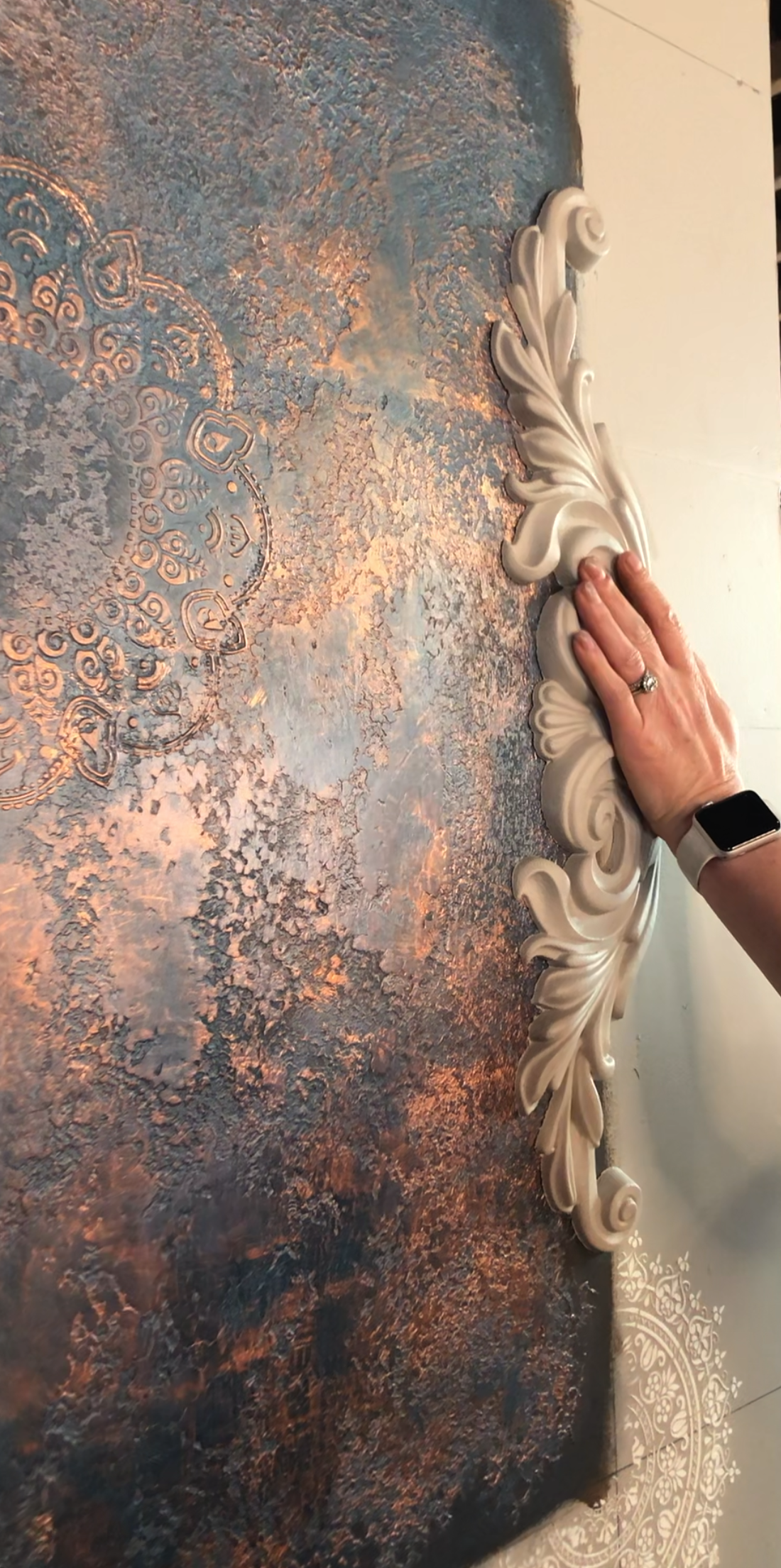 A hand pressing a pre-painted woodubend moulding onto a wall, blue and bronze texture can be seen in the foreground