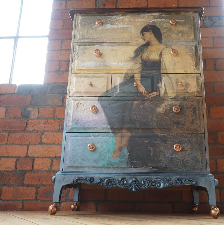 set of drawers featuring a decoupage design of a woman looking out to sea, the colours move from blues at the bottom into cream at the top