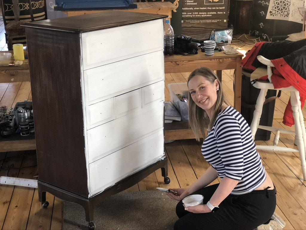 A stag chest of drawers, the front has been painted white, whilst the side has been left as is. To the right there is a smiling woman in front of it in a stripy top, she has just painted the project.