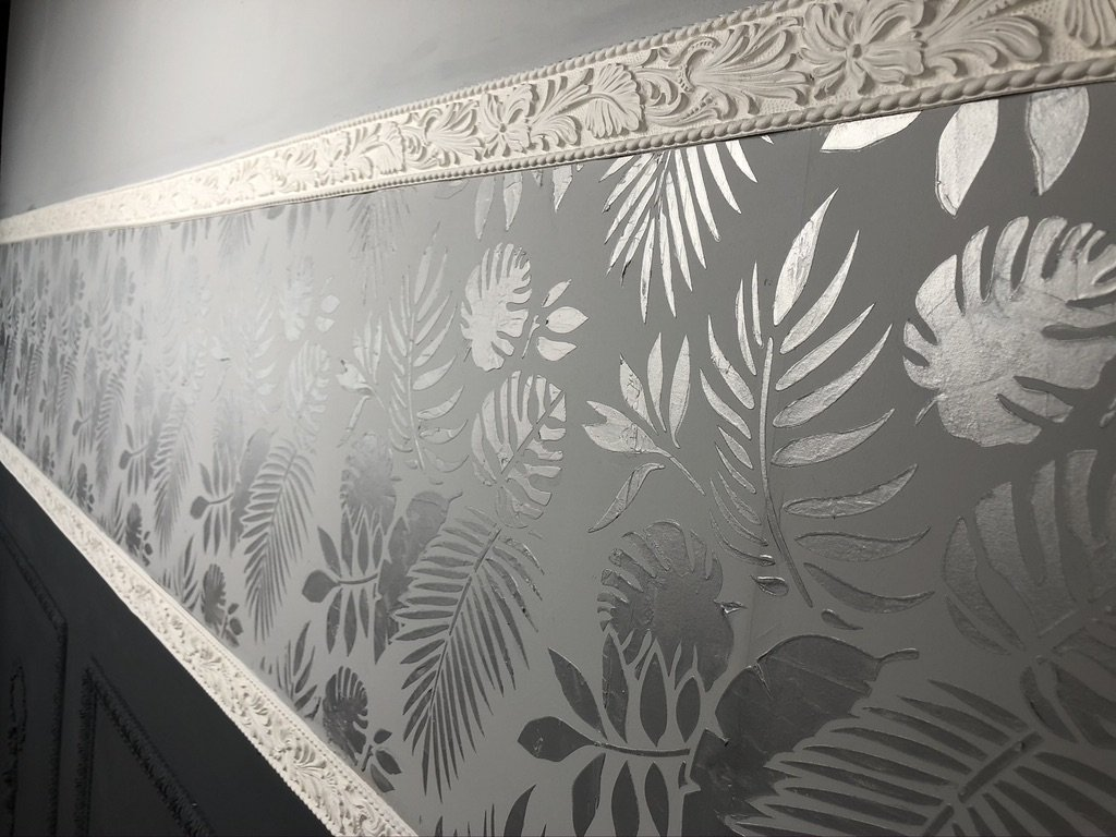 A grey wall split by two WoodUbend trims running parallel and roughly two feet apart. In the gap there is a tropical leaves pattern in silver created using Posh Chalk Stencils