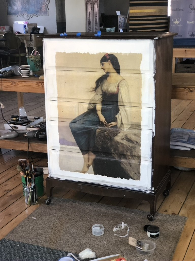 A chest of drawers painted in white with a decoupage design of a girl looking over her shoulder stuck to the front