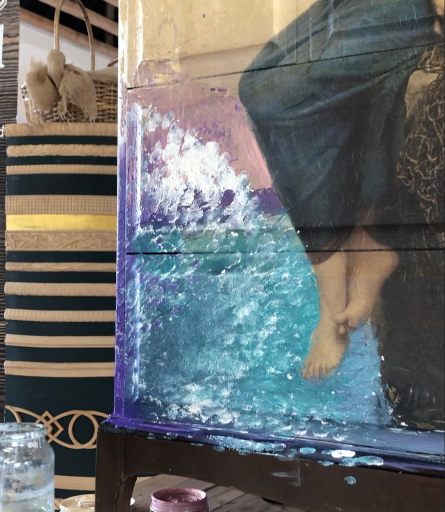 the bottom corner of a chest of drawers covered in blue paste with white finger marks over the top. The a decoupage design featuring the feet a lady can be seen in the right