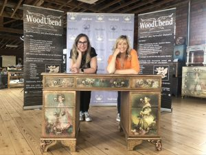 SollyJo and Sue Parsons leaning on the upcycled desk they have just completed. The desk has two decoupaged woman on either drawer down the side and decoupaged flowers across the top. It the background there are grey and dark brown banners displaying the WoodUbend and Posh Chalk logos.