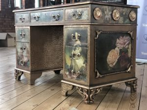 A vintage desk staged on hard wood and adorned with woodubend and decoupage