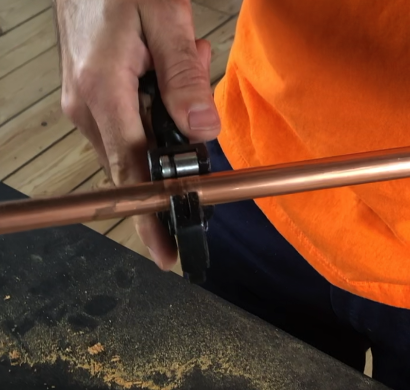 Copper Pipe being cut with a pipe cutter