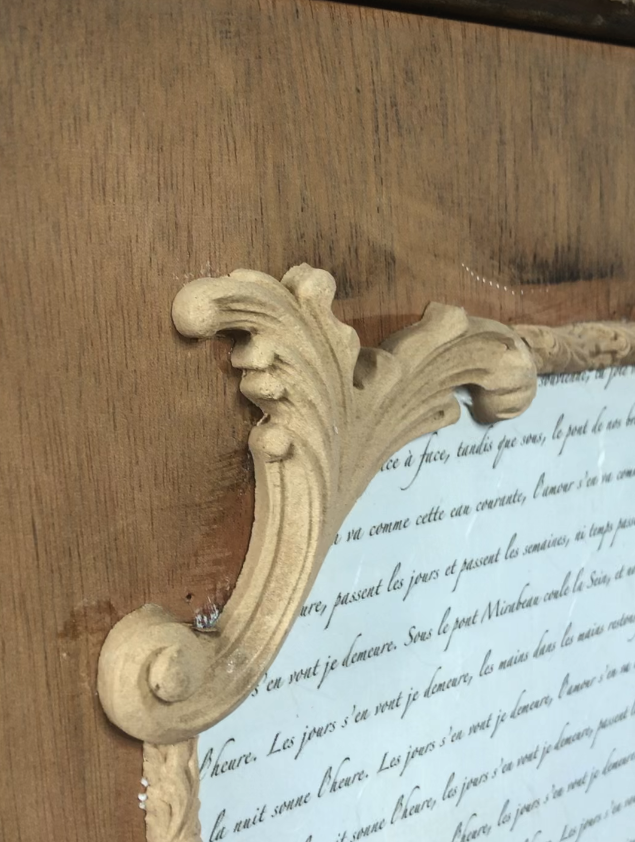 a close up of the 1338 woodubend moulding stuck to a upcycled desk, framing the Posh Script decoupage