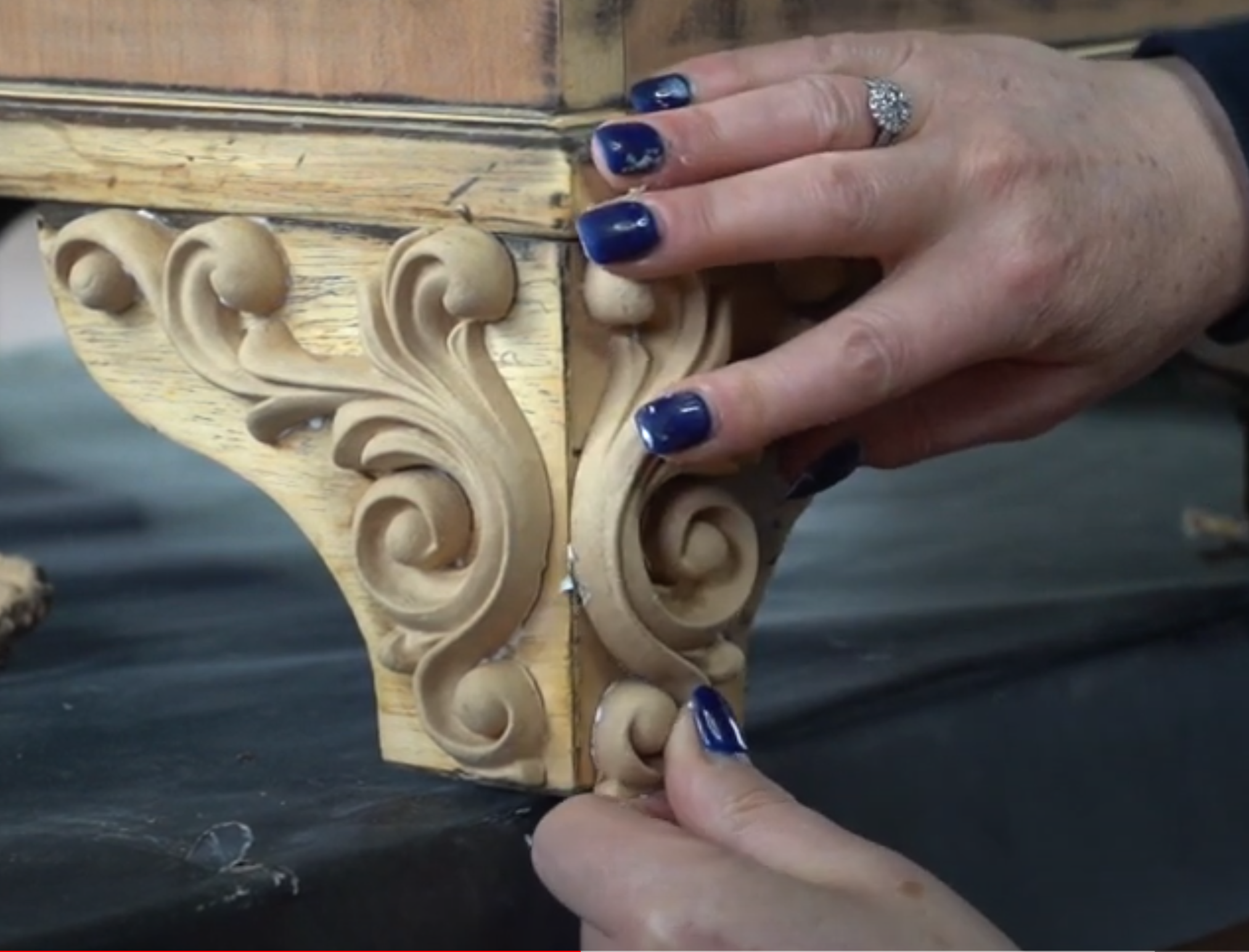 1239 WoodUbend mouldings being held in place on the feet of an upcycled desk by a woman with blue nails. In the forground you can see one moulding which has already stuck