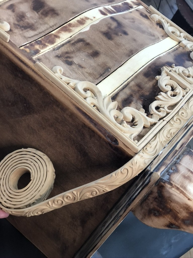 flexible wood trim being placed around the bottom of an unpainted, brown chest of drawers. The cooild of the woodUbend trim can be seen in the bottom left.