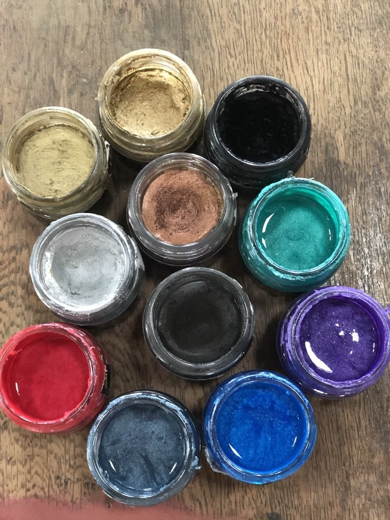 A selection of Posh Chalk Patinas and Aqua Patinas in a variety of colours against a brown wooden background. All the lids have been removed so the colours inside the pots can be seen.