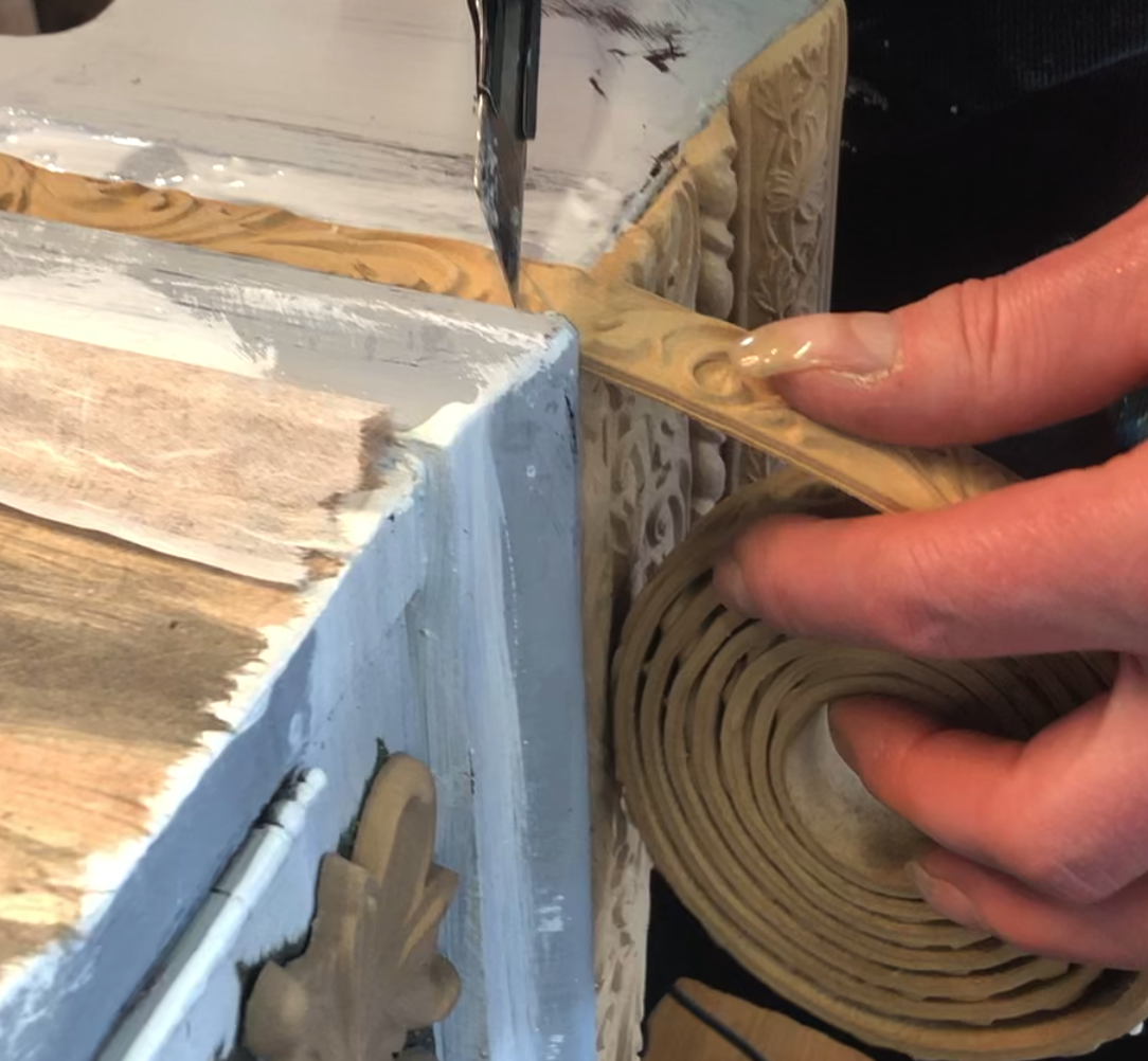 A bendable wood trim in it's coil about to be sliced with a craft knife