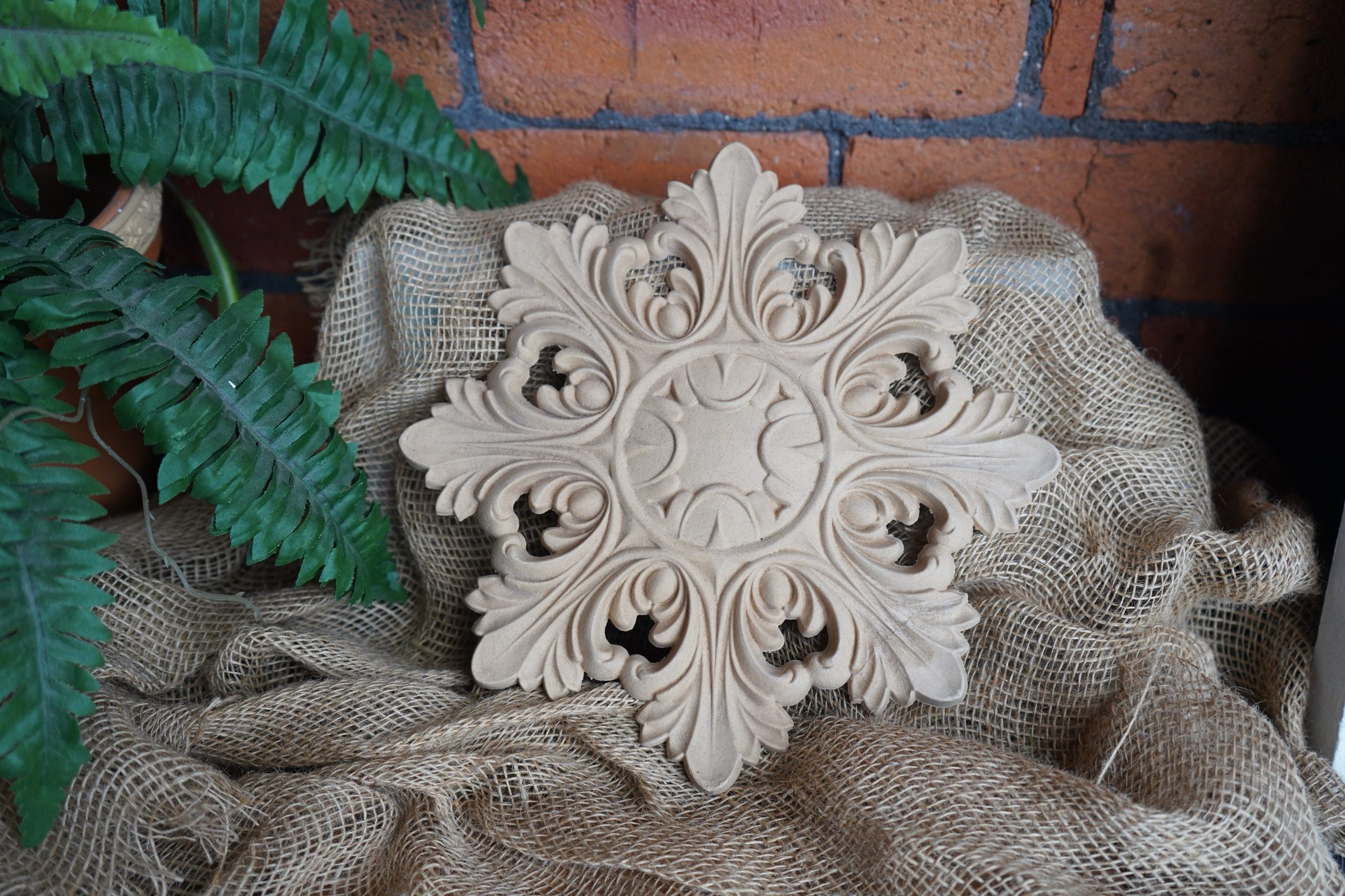 A bare bendable wood moulding in the shape of a star. It's sat on some hessian against a red brick background with green ferns on the left hand side.