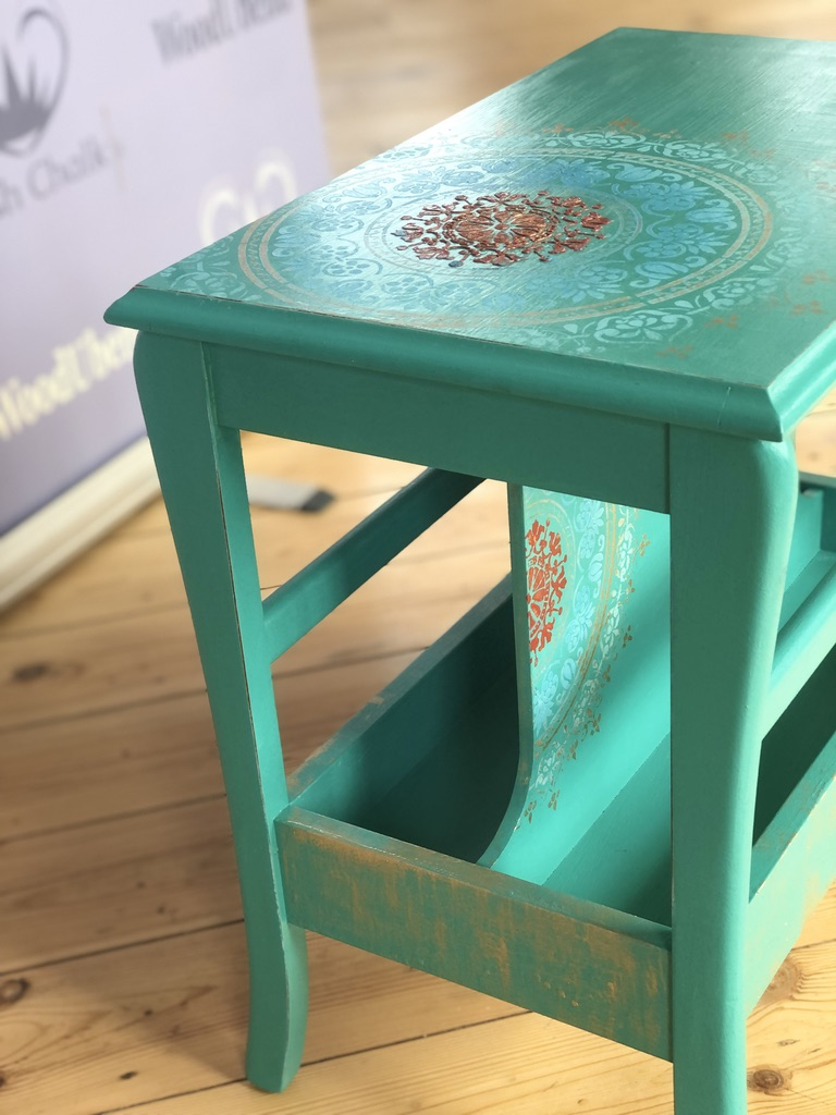 A red and blue Pish Chalk Spider Mandala stencilling pattern on a green table