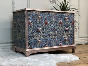 A furniture makeover project with blue decoupage and rose gold accents