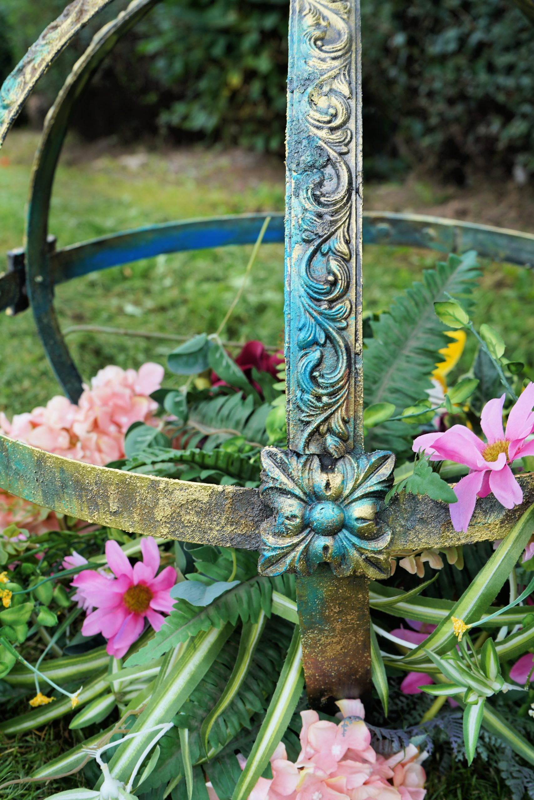 An armillary sphere outside on the grass. Blues, golds and creeens coat the decorative mouldings on it whilst flowers sit inside