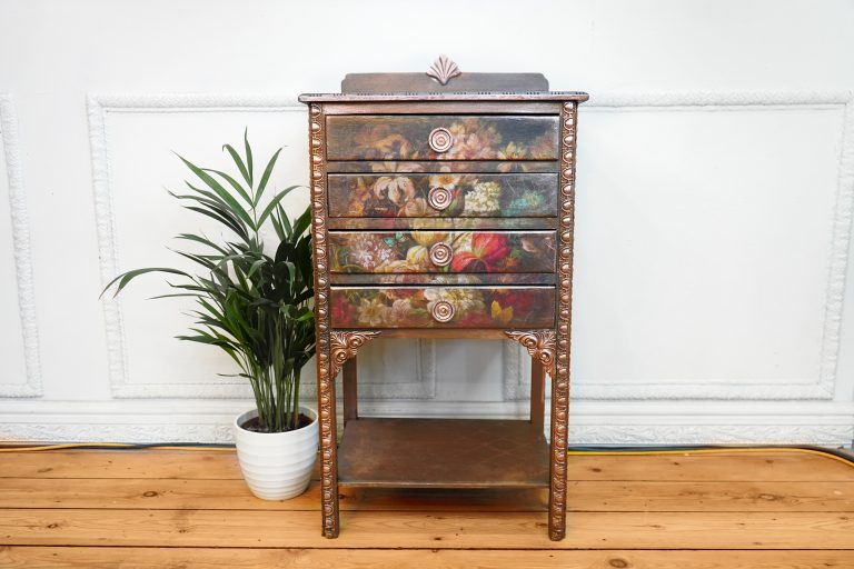 A set of drawers staged against a white wall. Decoupage covers the front and the deep gold posh chalk paste gives the bare wood a full bodied feel.
