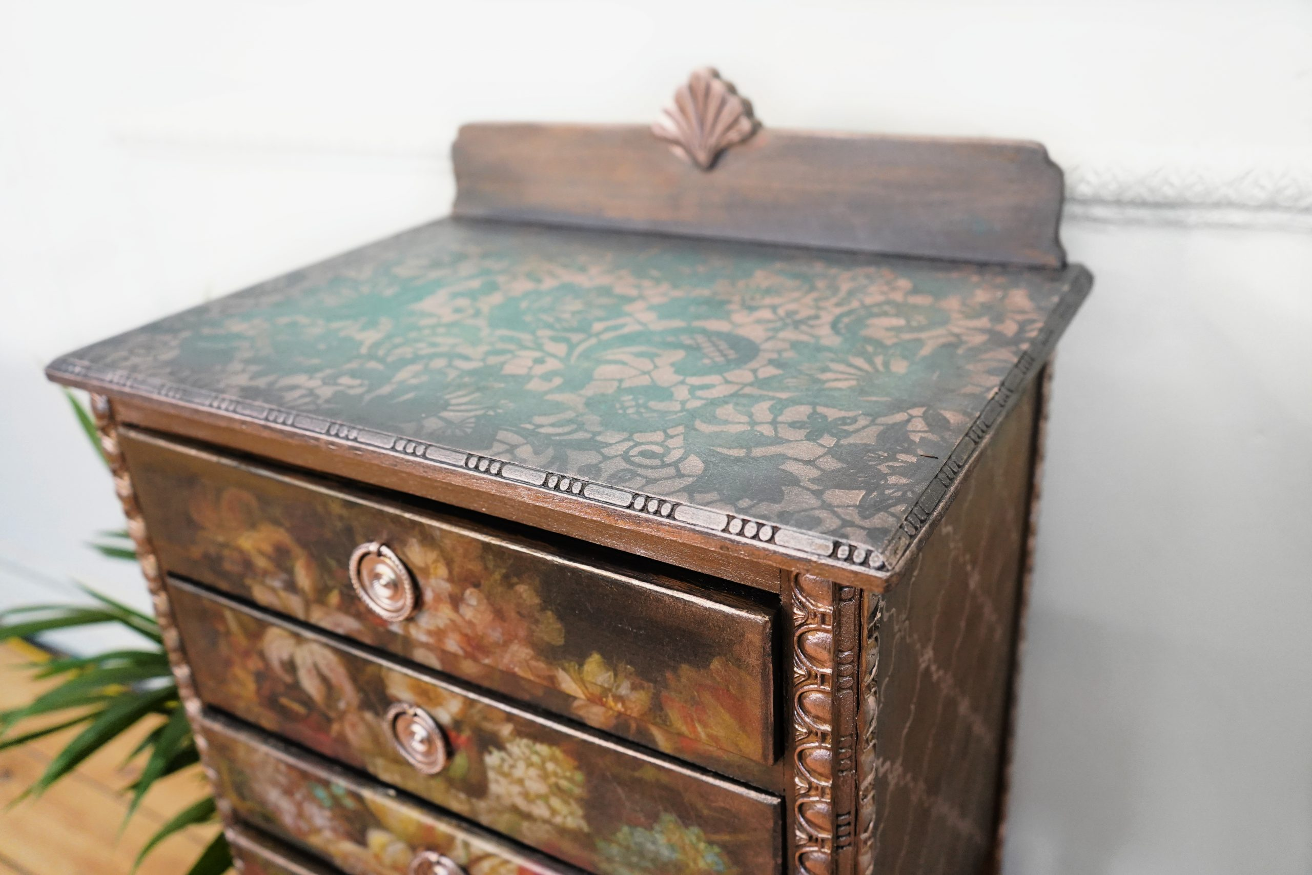 A set of drawers with decoupage on the front and washed with posh chalk pastes in gold and green. Rose gold pigments pick out the finer details of the woodubend trims on the side.