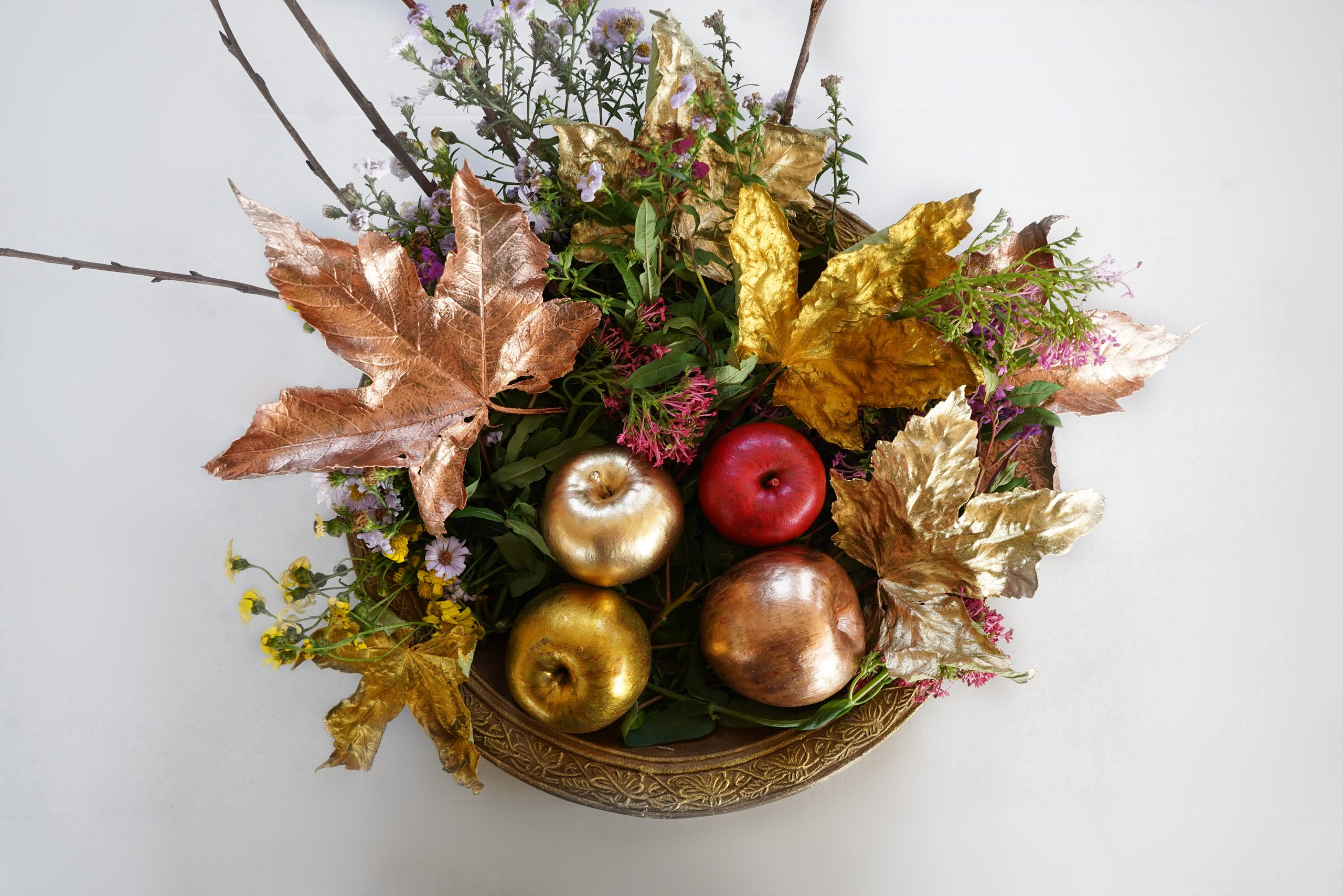 A collection of autumn craft ideas including painted leaves and apples together in a bowl.