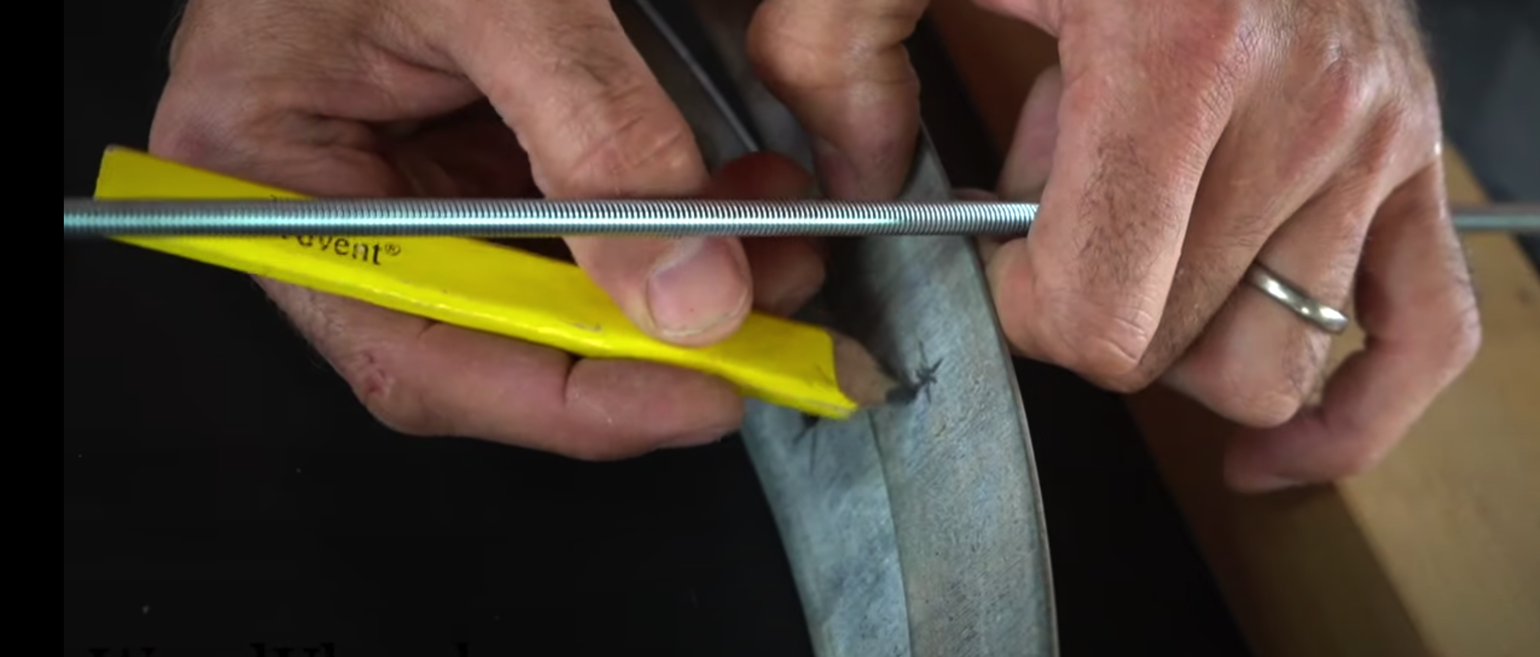 A yellow pencil being used to mark up a metal hoop. A metal bar is used as a guide of where to mark.
