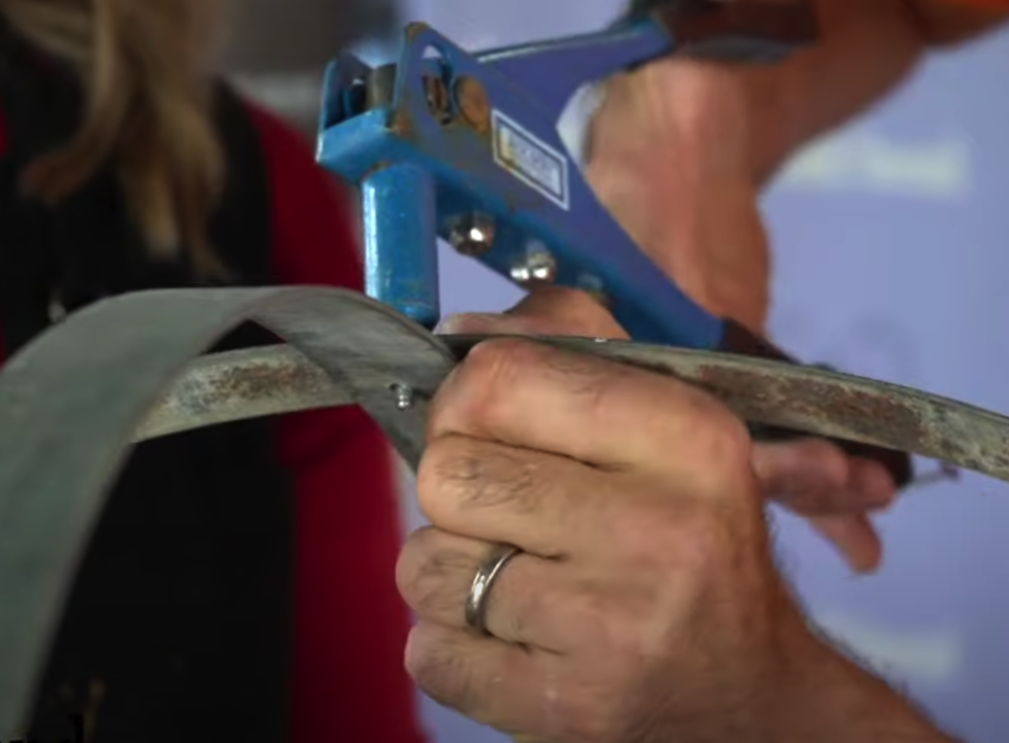 A rivet gun being used to join two barrel hoops together