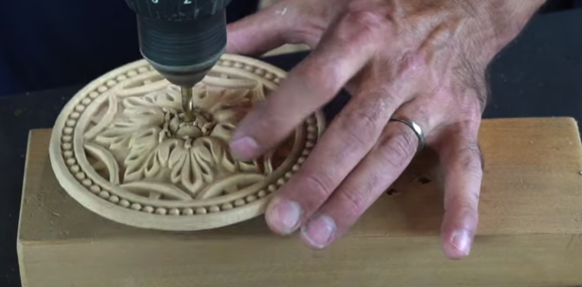 A WoodUbend moulding being drilled on a block of wood
