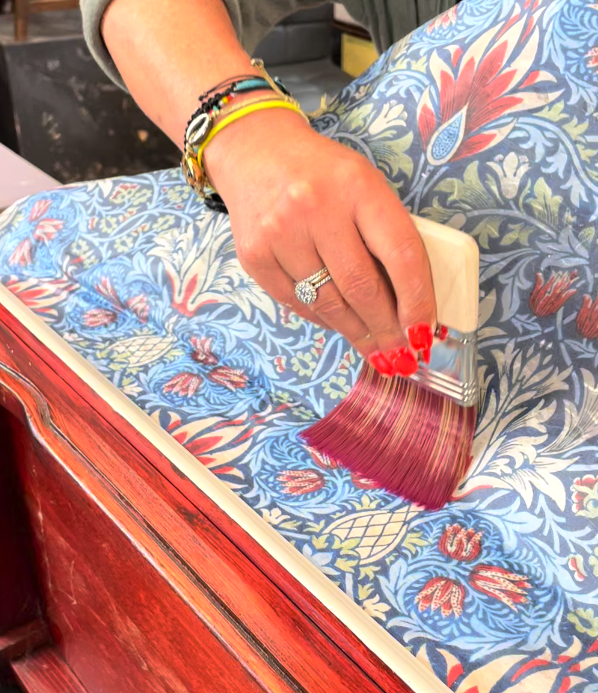 Decoupage paper being laid onto a furniture makeover project using a dry paintbrush. The decoupage is mainly blue and features a lively pattern.