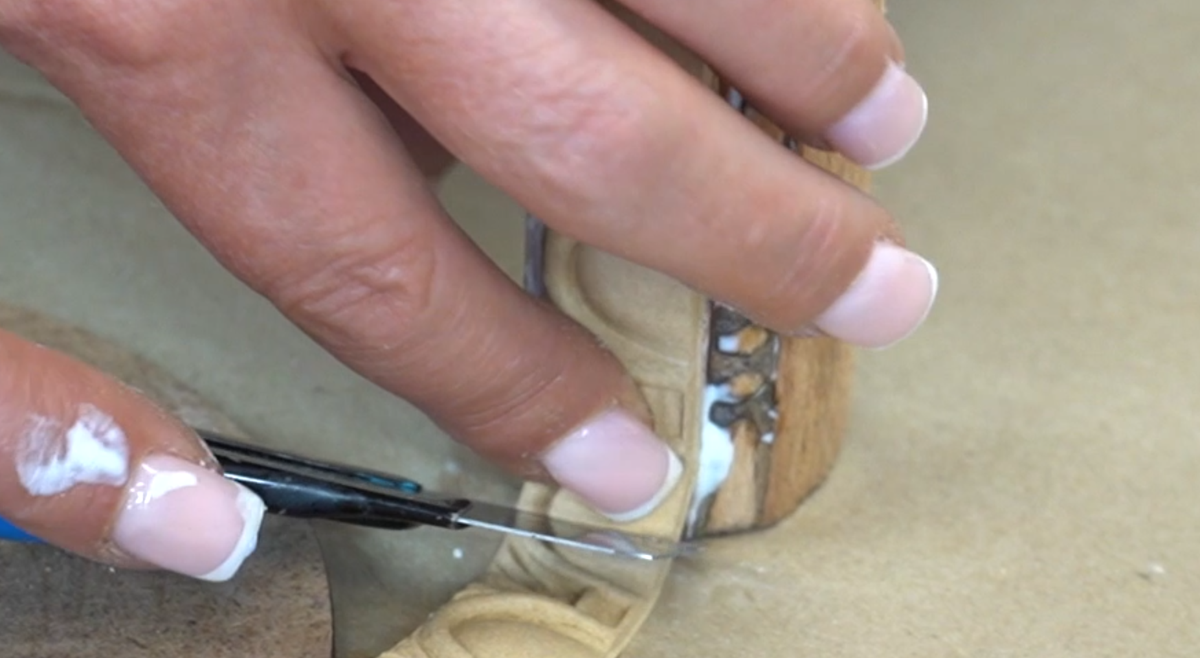 A close up of a WoodUbend trim being sliced with a craft knife