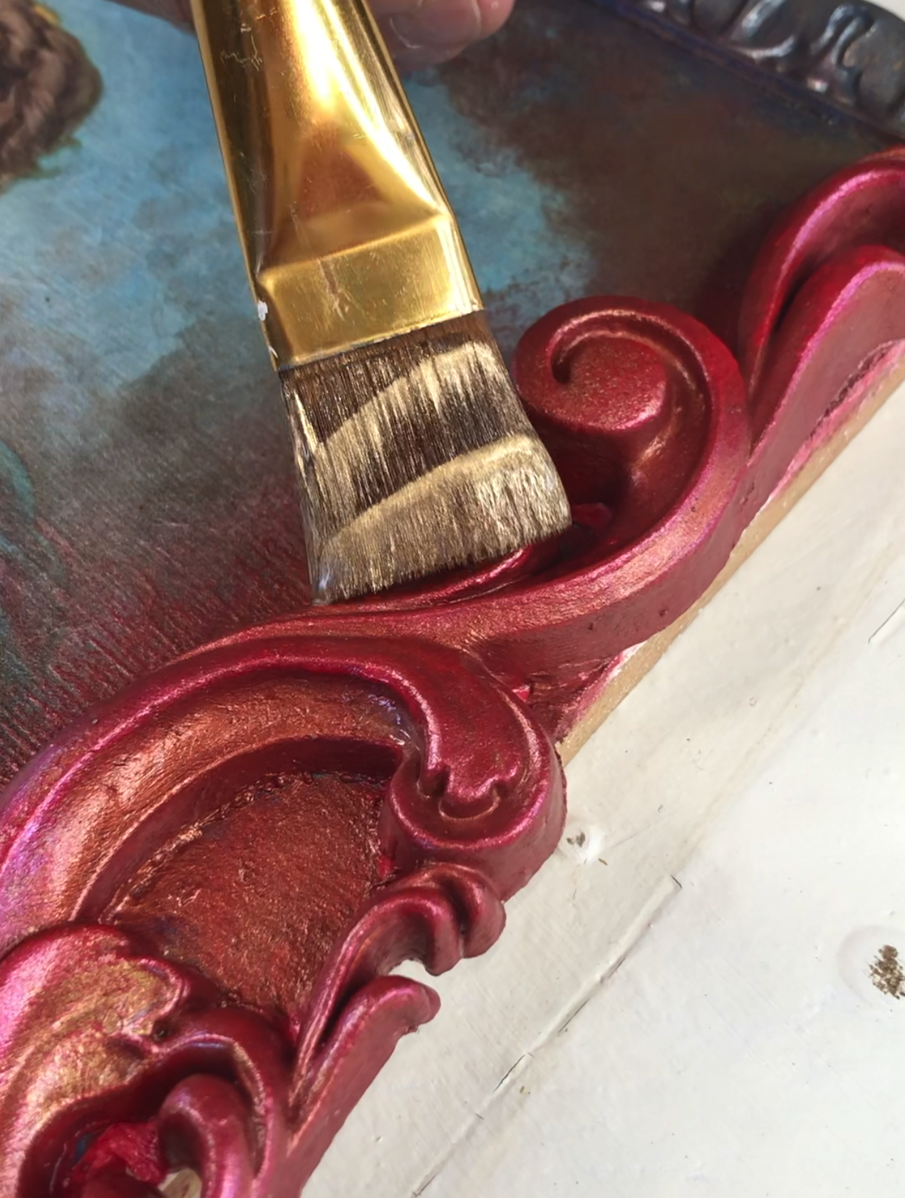 A close up of the 6069 woodubend moulding being painted with the gold posh chalk aqua patina